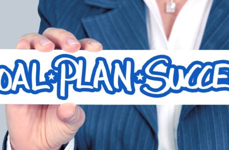 Image of business woman holding up a sign that reads goal-plan-success.